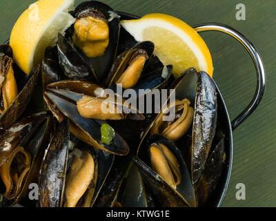 Muscheln in einer Knoblauch und Schalotten-Sauce mit Zitronenscheiben gewachsen Seil
