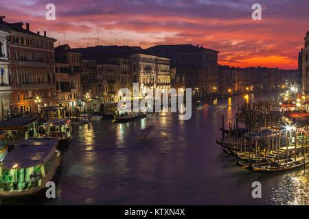 Bunte kalten Winter Sonnenuntergang über den Canal Grande, von der Rialto Brücke, Venedig, Italien mit Vaporetto und Gondeln, Dämmerung, Nacht