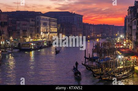 Gondeln auf dem Canal Grande bei Sonnenuntergang von der Rialto Brücke, Venedig, Italien mit Licht im Winter Nebel, Dämmerung, Nacht