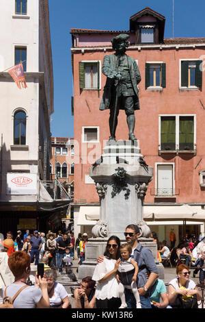 Eine junge Familie vor der Statue des berühmten venezianischen playright Carlo Goldoni, Venedig posing - Stockfoto