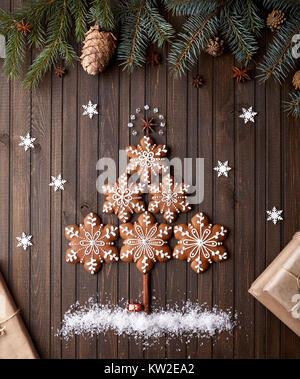 Weihnachtsbaum aus Lebkuchen Sterne mit Schnee rund um auf rustikalen braunen Hintergrund