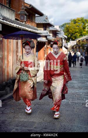 Zwei schöne Maiko, Geisha Auszubildende in farbenprächtige Kimonos zu Fuß auf einer alten Straße Yasaka Dori in - Stockfoto