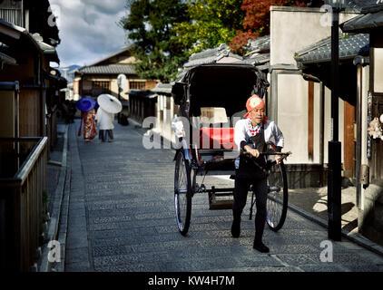 Japanische Rikscha auf einer alten Straße in Kyoto mit ein paar Kimonos tragen im Hintergrund. Yasaka Dori, in der - Stockfoto