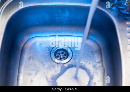 Ein Bach mit sauberem Wasser fließt in das Waschbecken aus Edelstahl in blau Tönen. Waschbecken aus Edelstahl Öffnung - Stockfoto