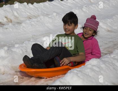 Kinder Schlitten reiten auf Lastwagen - im Schnee bei Drake Park in Long Beach, CA, USA - Stockfoto