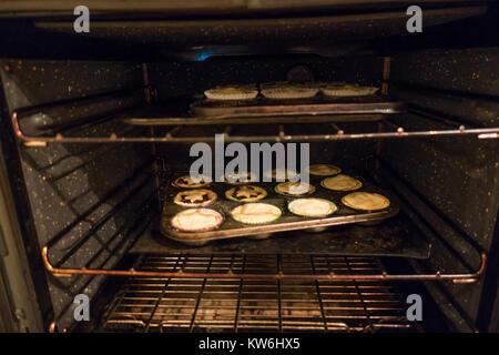 Die Mince Pies: Zwei Kuchenbleche mit Mince Pies in einem heißen Ofen backen, gefüllt sind. 15 der 16. - Stockfoto
