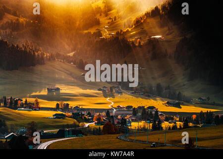 Beleuchtung Sonnenstrahlen durch die Wolken und fiel in dem kleinen Dorf auf dem Hügel, lebendige Farben des Sonnenuntergangs, - Stockfoto