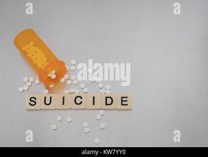 Die Suicide mit Fliesen Buchstaben in einer Reihe mit einer offenen Flasche oxycodone Tablets platziert geschrieben. - Stockfoto