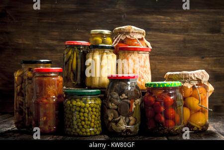 Konserven Gemüse und Pilzen, die in Gläsern. Auf einer hölzernen Hintergrund. - Stockfoto