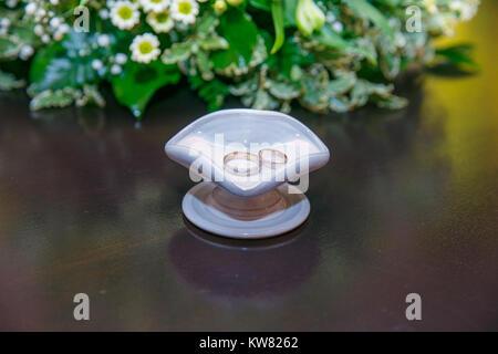 Zwei Ringe und grünen Blättern. Lettland. Kunst Hochzeiten Foto. 2017 - Stockfoto