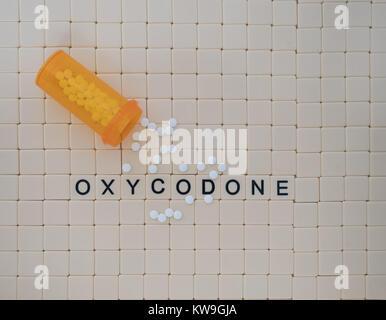 Oxycodone in Großbuchstaben in beige Kacheln mit schwarzen Buchstaben geschrieben. Eine geöffnete Flasche Tabletten - Stockfoto