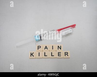 Schmerzmittel mit Fliesen Buchstaben in einer Reihe mit einem Fertigspritze mit klarer Flüssigkeit und ein leeres - Stockfoto
