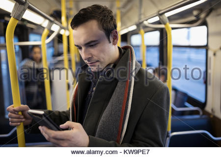 Geschäftsmann Pendler texting mit Smart Phone auf Bus - Stockfoto