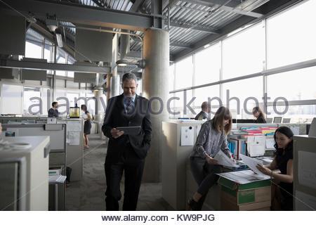 Geschäftsmann zu Fuß und mit digitalen Tablette im Großraumbüro - Stockfoto