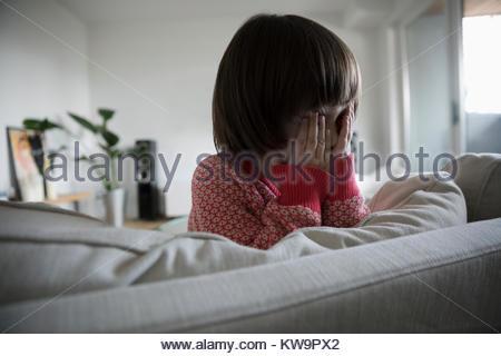 Süß, schüchtern Kleinkind Mädchen verstecken Gesicht in die Hände auf Sofa im Wohnzimmer - Stockfoto