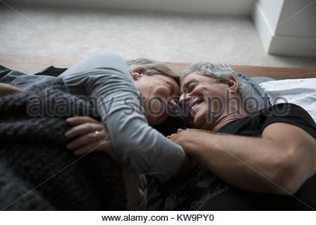 Zärtlich, romantisch Senior paar Kuscheln im Bett - Stockfoto