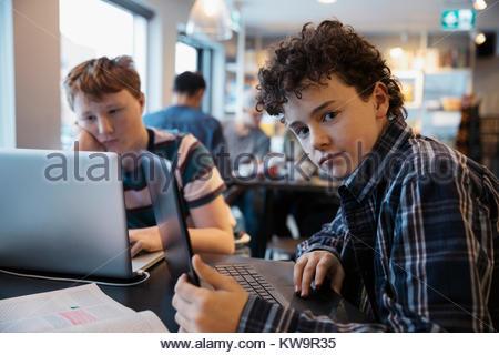Portrait ernst, zuversichtlich High School junge Studenten studieren an Laptop im Cafe - Stockfoto