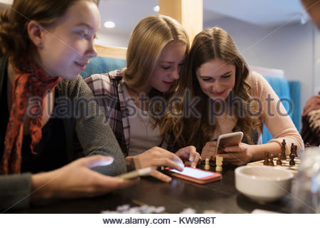 Tween girl friends Schach spielen und texting mit Smart Phones im Cafe Tabelle - Stockfoto