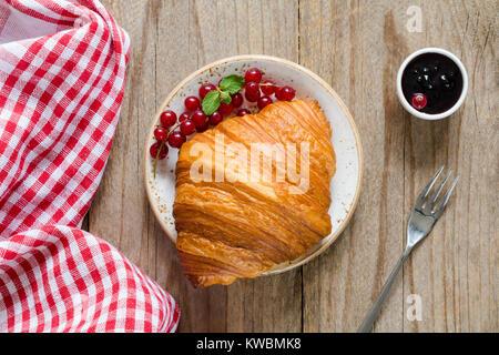 Croissant mit frischen Beeren und Marmelade auf alten Holztisch. Ansicht von oben, horizontal - Stockfoto