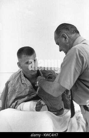 Präsident Lyndon Johnson vergibt eine Medaille an einem verwundeten US-Soldaten. Nocken Rahn Bucht, Südvietnam. - Stockfoto