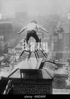 """""""Menschliche Fliegen 'John' Jammie """"Reynolds Salden geneigt, der unsicher auf zwei Stühlen. Das dare-devil ist auf - Stockfoto"""