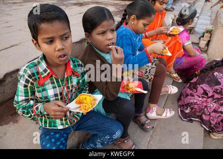 Kinder essen einen Snack von büchel puri an den ghats von Varanasi, Indien - Stockfoto