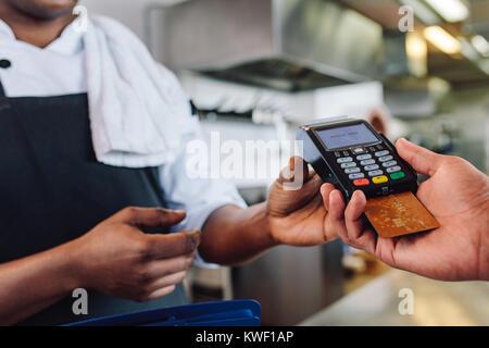 Der Kunde zahlt Restaurant Rechnung mit Kreditkarte. Kunden die Zahlung durch Kreditkarte am Zähler in einem Restaurant. - Stockfoto
