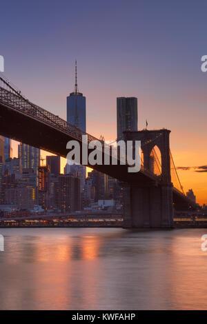 Brooklyn Bridge mit der New Yorker Skyline im Hintergrund, bei Sonnenuntergang fotografiert. - Stockfoto