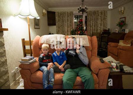 Enkel saß auf dem Sofa in einer traditionellen englischen Haus mit ihrem Großvater an Weihnachten während er am - Stockfoto