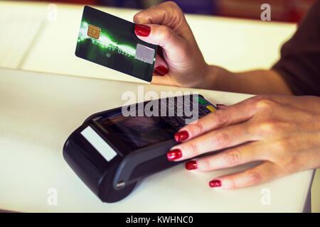 Hände Nahaufnahme von einem Verkäufer mit einem dataphone mit einer Kreditkarte in einem Geschäft Schreibtisch zu - Stockfoto
