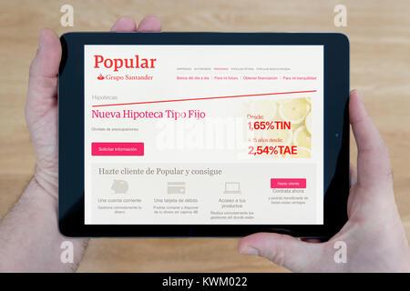 Ein Mann schaut auf die Banco Popular Website auf seinem iPad Tablet Vorrichtung, die auf einer hölzernen Tisch - Stockfoto