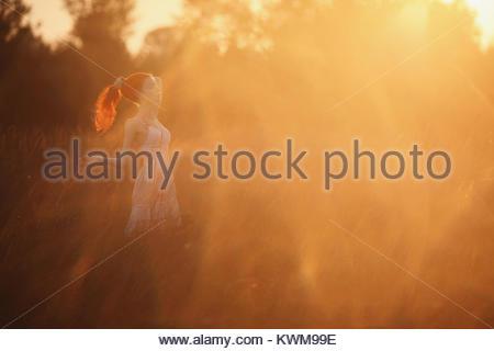 Eine Frau mit rotem lockigem Haar in Weiß sundress auf dem Hintergrund der Morgenröte. Rothaarige Mädchen mit blasser - Stockfoto