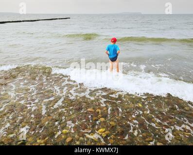 Junge in Blau Schwarz sportliche Kleidung Aufenthalt in kalten schäumende Meer. Blonde Haare Kind in Wellen am steinigen - Stockfoto
