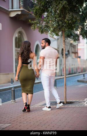 Glückliches Paar zu Fuß auf dem Bürgersteig Hand in Hand - Stockfoto