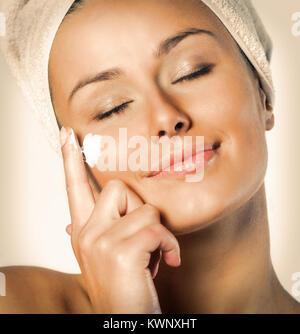 Schöne, junge Frau im Handtuch Verbreitung Creme im Gesicht umhüllt, Schuß auf weißem Hintergrund, - Stockfoto
