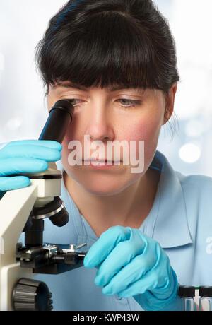 Portrait einer jungen Wissenschaftlerin Analyse rot flüssige Proben unter dem Mikroskop - Stockfoto