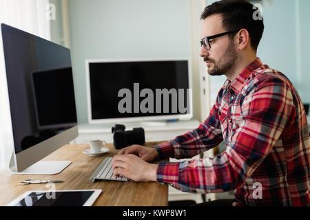 Junge schöne Designer, die am Projekt auf dem Computer - Stockfoto
