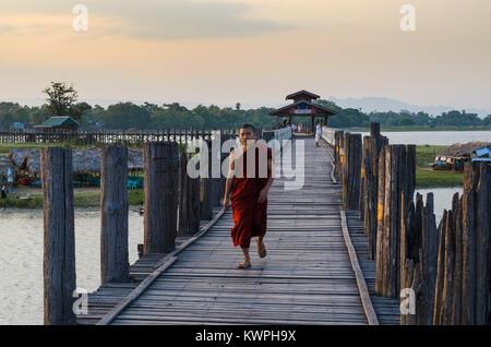 MANDALAY, MYANMAR - 3 Jan 2014: Ein buddhistischer Mönch Spaziergänge auf den U-Bein Brücke aus Teakholz bei Sonnenaufgang, - Stockfoto