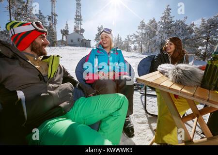 Gerne männliche und weibliche Skifahrer sprechen und lächelnd in Cafe auf Gelände - Stockfoto