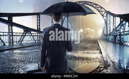 Elegante Mann hält einen schwarzen Regenschirm - Stockfoto