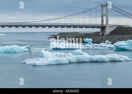 Eisbergen auf der Gletscherlagune Jokulsarlon kalben aus dem Gletscher Breiðamerkurjökull, im Südosten von Island, und fließt zum Meer unter einer Brücke Stockfoto