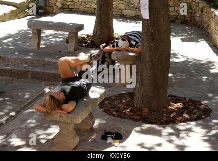 Ein Mann schläft auf einer Steinbank neben Cala Finestrat Strand in ...
