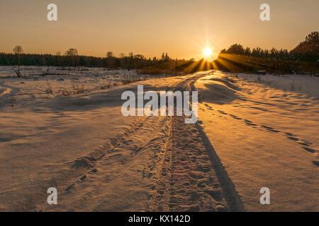 Lonely Trail von Snowmobile verschwinden in Abstand im Winter, bei Sonnenuntergang. - Stockfoto
