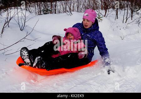 Ein Jugendlicher (18 Jahre alt) in einem Schlitten mit einem jungen Kind (3 Jahre alt), nervös wie viel schneller - Stockfoto