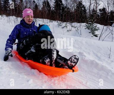 Ein Jugendlicher (18 Jahre alt) in einem Schlitten mit einem jungen Kind (5 Jahre alt), nervös wie viel schneller - Stockfoto