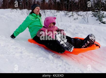 Eine erwachsene Frau in einem Schlitten mit ein kleines Mädchen (3 Jahre alt) Suchen Sie nervös wie viel schneller - Stockfoto