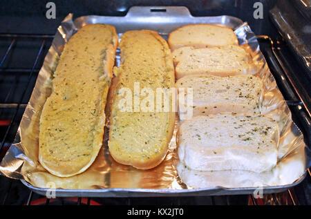 Köstliche buttrige Knoblauch Brot Kochen in Alufolie im Ofen - Stockfoto