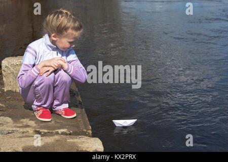 Mädchen sieht aus wie ein Papier Boot schwimmt auf dem Fluss - Stockfoto