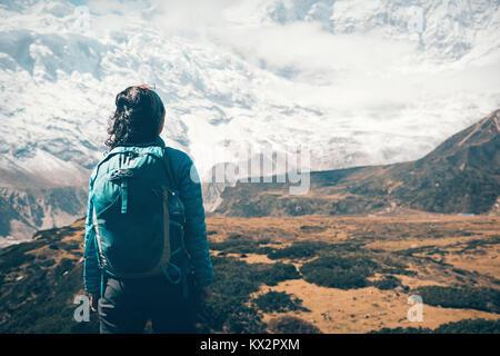 Stehende Frau mit Rucksack auf schöne schneebedeckte Berge in Wolken bei Sonnenuntergang. Landschaft mit Mädchen, - Stockfoto