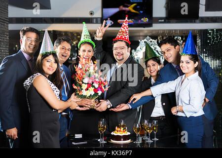 Gruppe Unternehmer und Unternehmerinnen. Partner Geburtstag geben Blumenstrauß feier Party-Hotel - Stockfoto